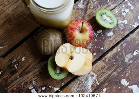 Fruit and milk drink on a wooden background. Kiwi apples on a dark background. Subject of obesity and health.