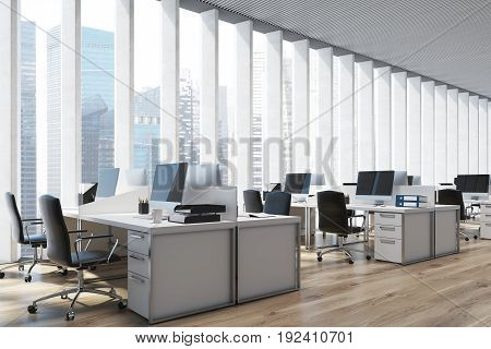 Close up of an open space office interior with a wooden floor a panoramic window with shades rows of computer tables and office chairs. 3d rendering mock up