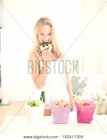Portrait of happy woman eating cookie at kitchen counter