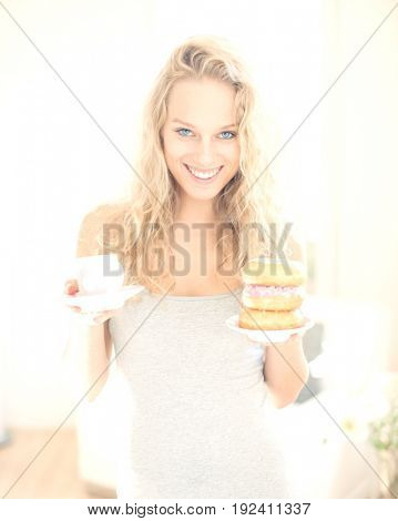 Portrait of happy woman with tea and donut in house