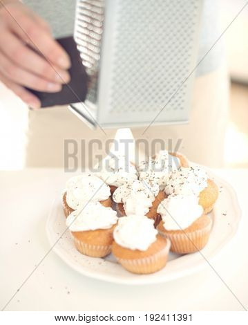 Cropped image of woman grating chocolate on cupcakes at counter