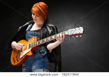 Portrait of young pretty girl with red hair playing guitar over black background. Copy space.