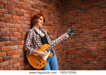 Portrait of young pretty girl with red hair playing guitar over brick background. Copy space.