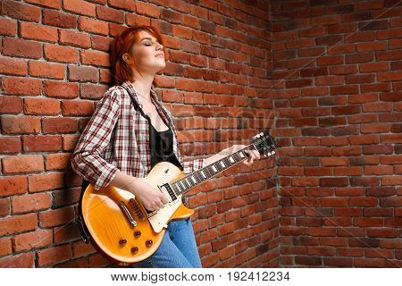 Portrait of young pretty girl with red hair playing guitar, eyes closed over brick background. Copy space.