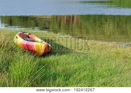 canoe in the grass in the shore of a lake