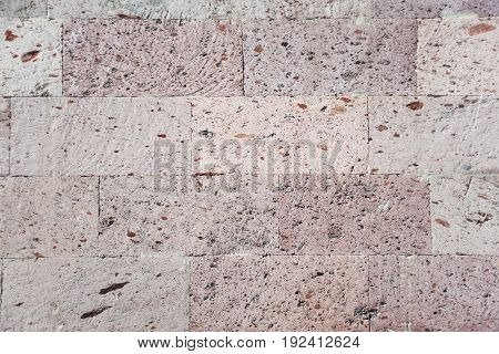 Abstract background: a wall of natural building stone pink tuff
