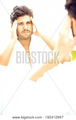 Reflection of man in bathrobe suffering from headache