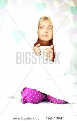 Portrait of young woman with coffee mug suffering from fever while wrapped in quilt on bed