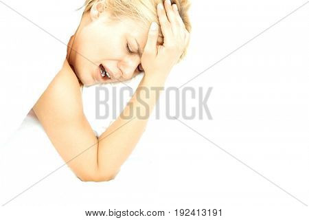 Young woman screaming while suffering from headache in bed