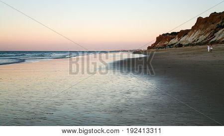 Tourists Walk On Beach Praia Falesia In Evening