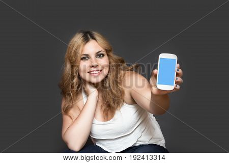 Studio shot of attractive long haired smiling teenage girl showing smart phone with blank touchscreen. The girl is holding her head by right hand. All is on the gray background. All potential trademarks and buttons are removed.