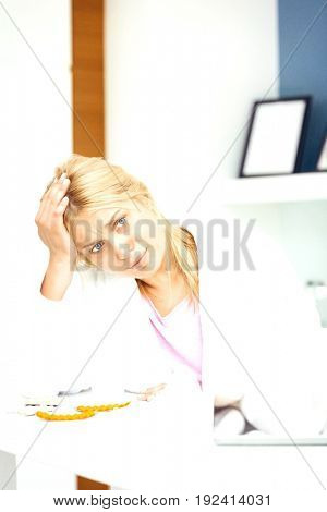 Young woman suffering from headache in kitchen