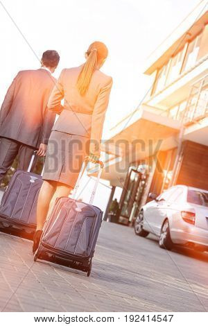 Back view of business couple walking with luggage on driveway