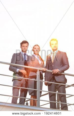 Low angle view of businesspeople standing on terrace against clear sky