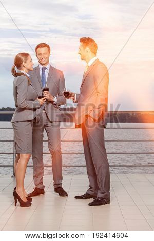 Full length of smiling businesspeople with wineglasses standing on terrace
