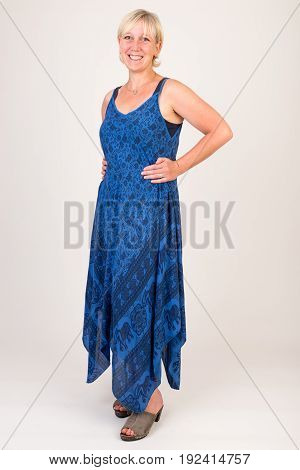 portrait of a attractive blond haired mid aged european woman wearing blue dress showin happy face - full body - studio shot on white background.
