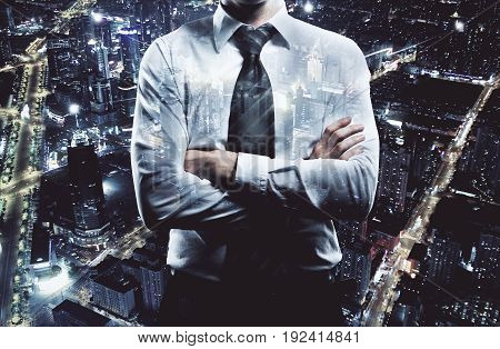 Businessman with folded arms on night city background. Employment concept. Double exposure