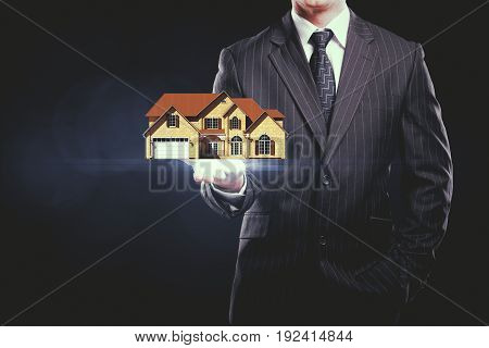 Businessman holding abstract house miniature on dark background. Real estate concept