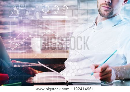 Young businessman doing paperwork and holding laptop at modern workplace with digital business charts. Financial growth. Double exposure