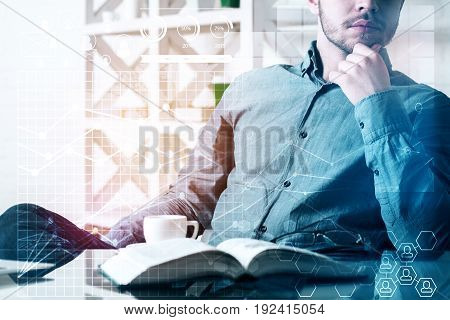 Thoughtful young businessman at workplace with open book coffee cup and digital business pattern. Online accounting concept. Double exposure