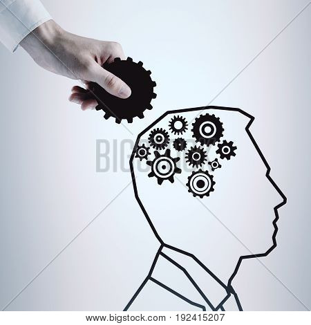 Hand putting cogwheels into drawn man's head on light background. Strategy concept