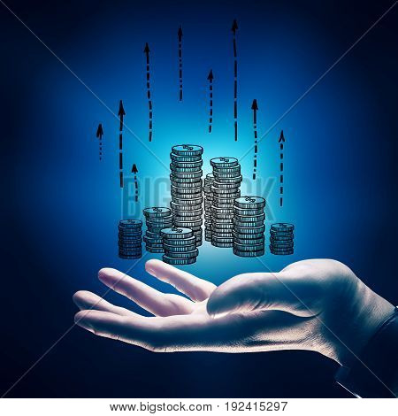 Side view of businessman's hand holding drawn coins with upward arrows on blue background. Financial growth concept