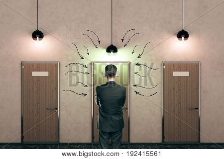 Businessman looking at wooden doors with drawn arrows and illuminated lamps in concrete interior. Choice concept. 3D Rendering