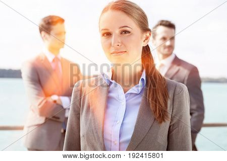 Portrait of confident businesswoman standing with coworkers in background on terrace