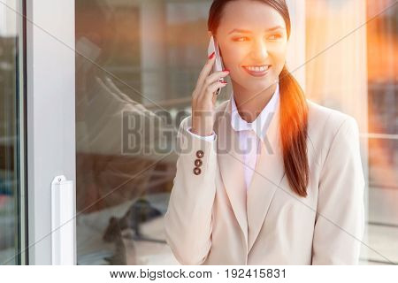 Happy businesswoman using cell phone by glass door