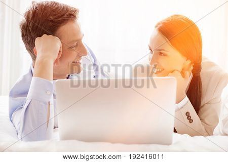 Happy business couple with laptop looking at each other in hotel