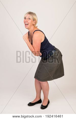 portrait of a attractive blond haired mid aged european woman wearing green skirt and blue top showing happy face - full body - studio shot on white background.