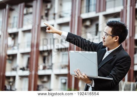 Business Concept - Young Business Man Plan Project On His Property With Laptop.