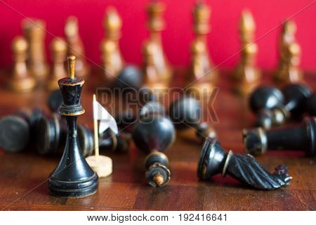 Ancient wooden chess pieces on an old chessboard. With the white flag of surrender. On a red background.