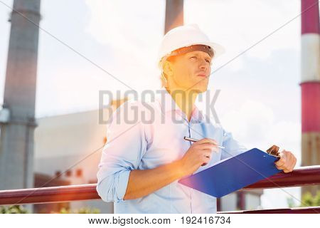 Male architect with clipboard and pen at site