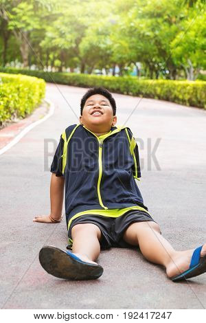 Sport concept - Little sport runner boy sit on the track and take a deep breath. Feel tired.