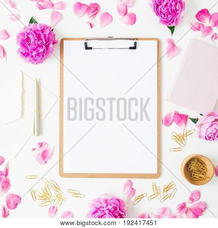 Workspace with clipboard, notebook, pen, envelope and pink roses on white background. Flat lay, top view.