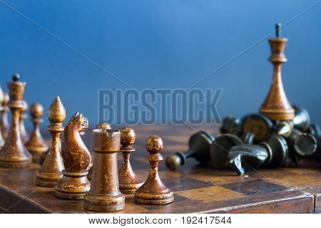 Ancient wooden chess pieces on an old chessboard. On a blue background.