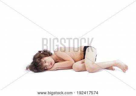 Little Curly-haired Boy In Shorts Sleeping On The Floor Cross-legged. Gray Background.