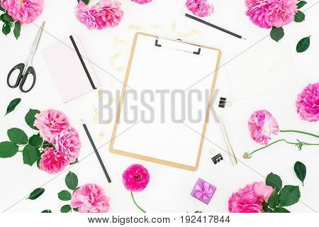 Styled wedding workspace with clipboard, notebook, pink roses, ranunculus and accessories on white background. Flat lay, top view.