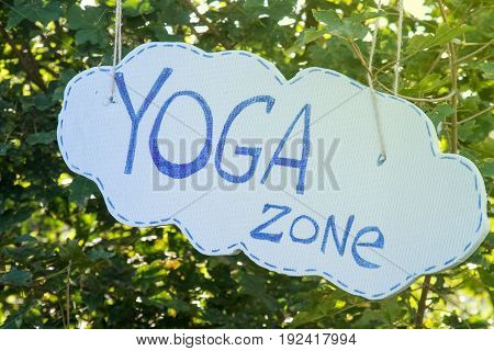 Inscription Yoga Zone on a background of green tree leaves.