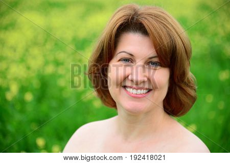 Portrait of a smiling middle-aged woman with bare shoulders