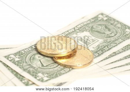 Golden bitcoin coins on us dollars isolated on white