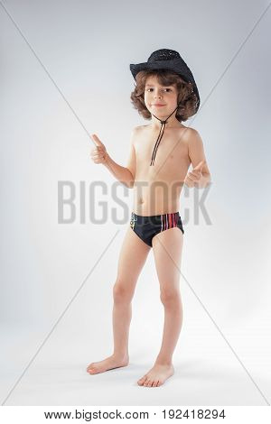 Little curly-haired cowboy hat and bathing suit standing and looking at the camera. Gray background.