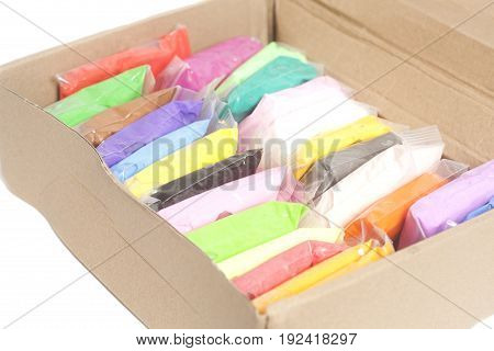 Colorful polymer clay in box isolated on white