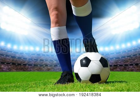 Soccer ball and foots of football player on stadium.