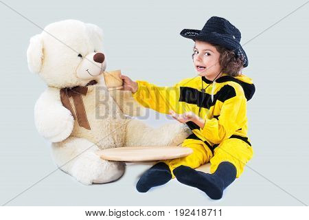 A cute boy in a bee costume feeds a bear. White background.