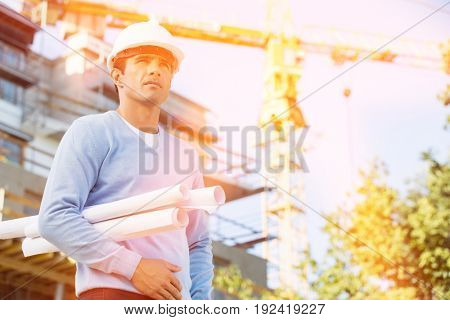 Male architect holding rolled up blueprints while standing at construction site