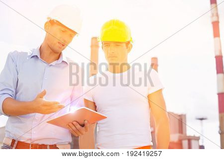 Male construction workers discussing over digital tablet at industry