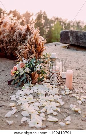 Original wedding floral decoration in the form of mini- bouquets of flowers and candles for ceremony. Outdoors wedding ceremony