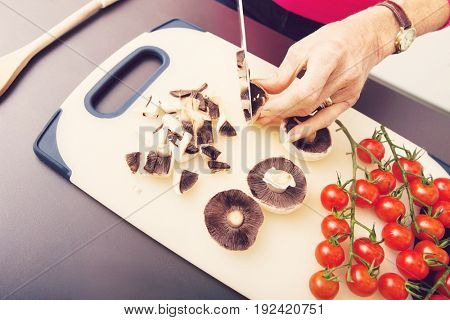 Senior woman's hand chopping mushrooms on cutting board